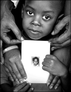Emmanuel Koyaweda 4, holds a photograph of his sister Kelly Koyaweda 9, with some help from his parents Emilienne Koyaweda and Firmin Koyaweda. Separated by the crisis in the Ivory Coast, these patient and persistent parents and brother never gave up hope that they would see their daughter again.Ê